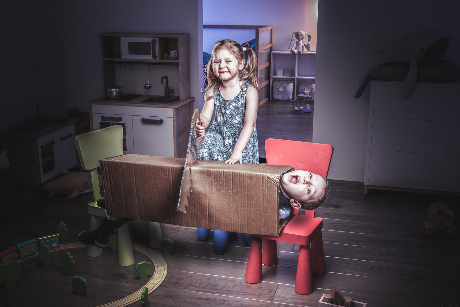 Young girl playing magician attempts to saw sister in half