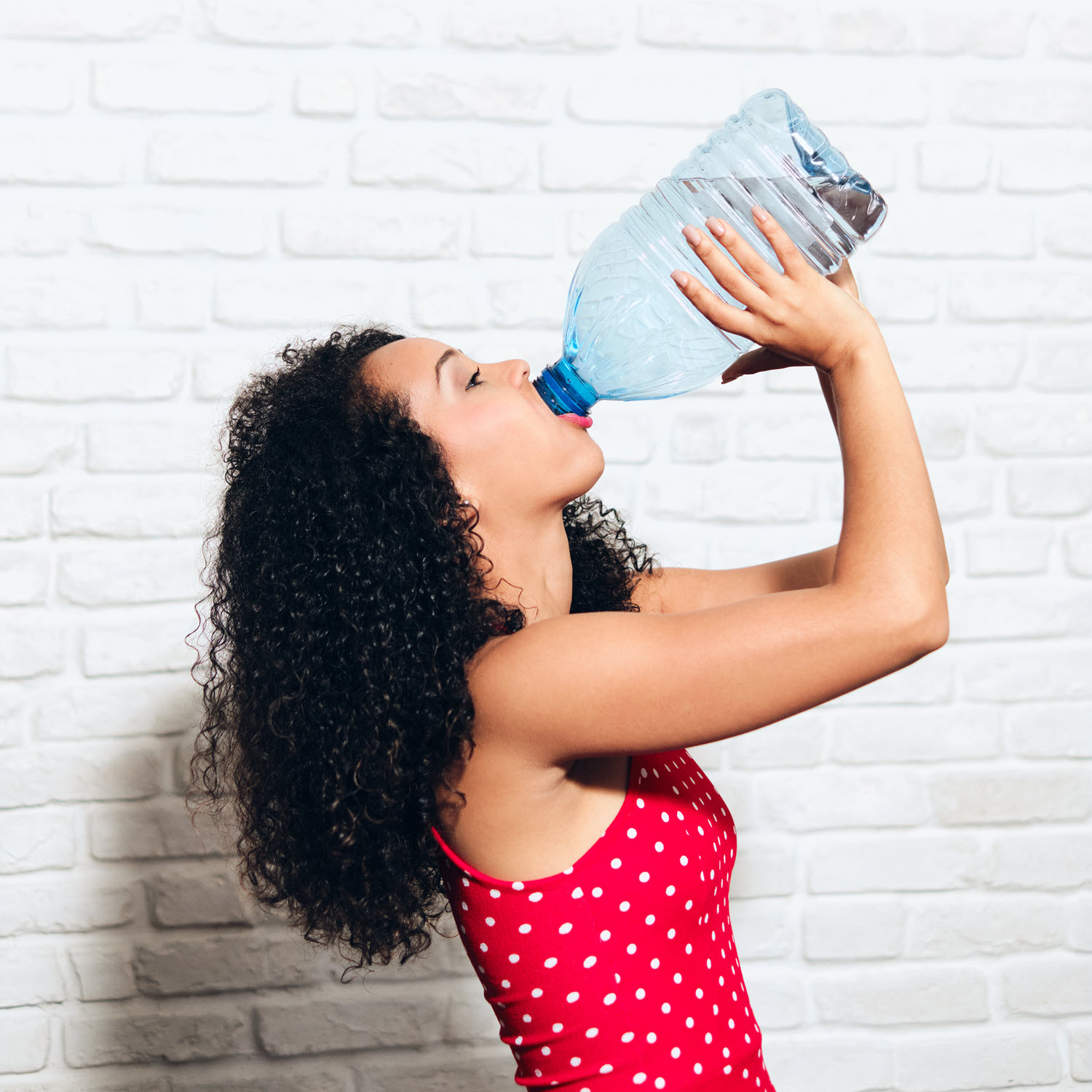Woman drinking water for hydration from a gallon bottle